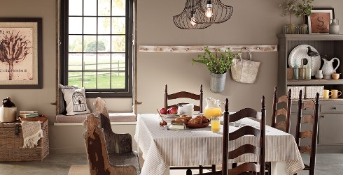 Farmhouse rustic dining room, walls in creamy beige, dining table surrounded by wooden slat chairs and rustic wooden bench.