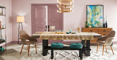 Casually styled dining space, walls in soft muted pink accented with mauve-pink trim and doors, modern chandelier and Saarinen chairs.