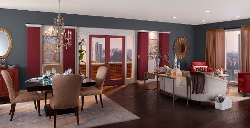 Open concept dining space, modern elegance, walls in rich blue-gary with crimson accent pillars, modern slipper dining chairs surround ebonized table.