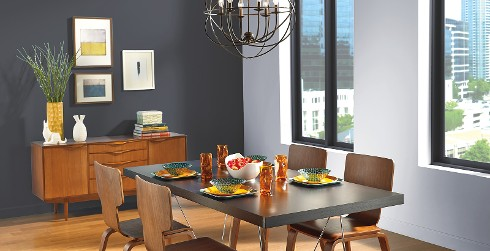 Modern dining space with accent wall in dark gray and window wall pale gray, rectangular dining table with modern dining chairs.