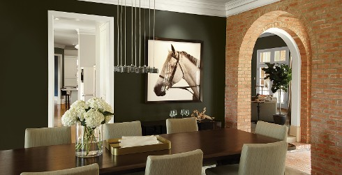 Contemporary farmhouse dining room with dark forest green on walls and white trim, brick accent wall surrounds an arched entryway.