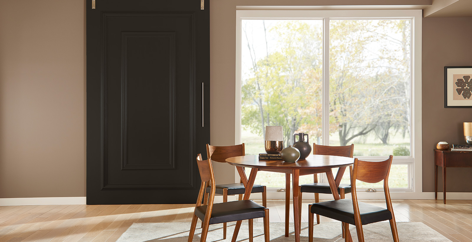 Open dining space in front of sliding doors, walls painted in warm tan color with white trim, sliding barn door in espresso black.