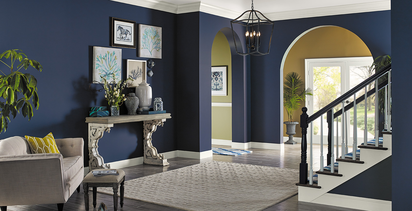 Hallway with stairs, dark navy walls, white trim, and vintage furniture, bold and sophisticated style.