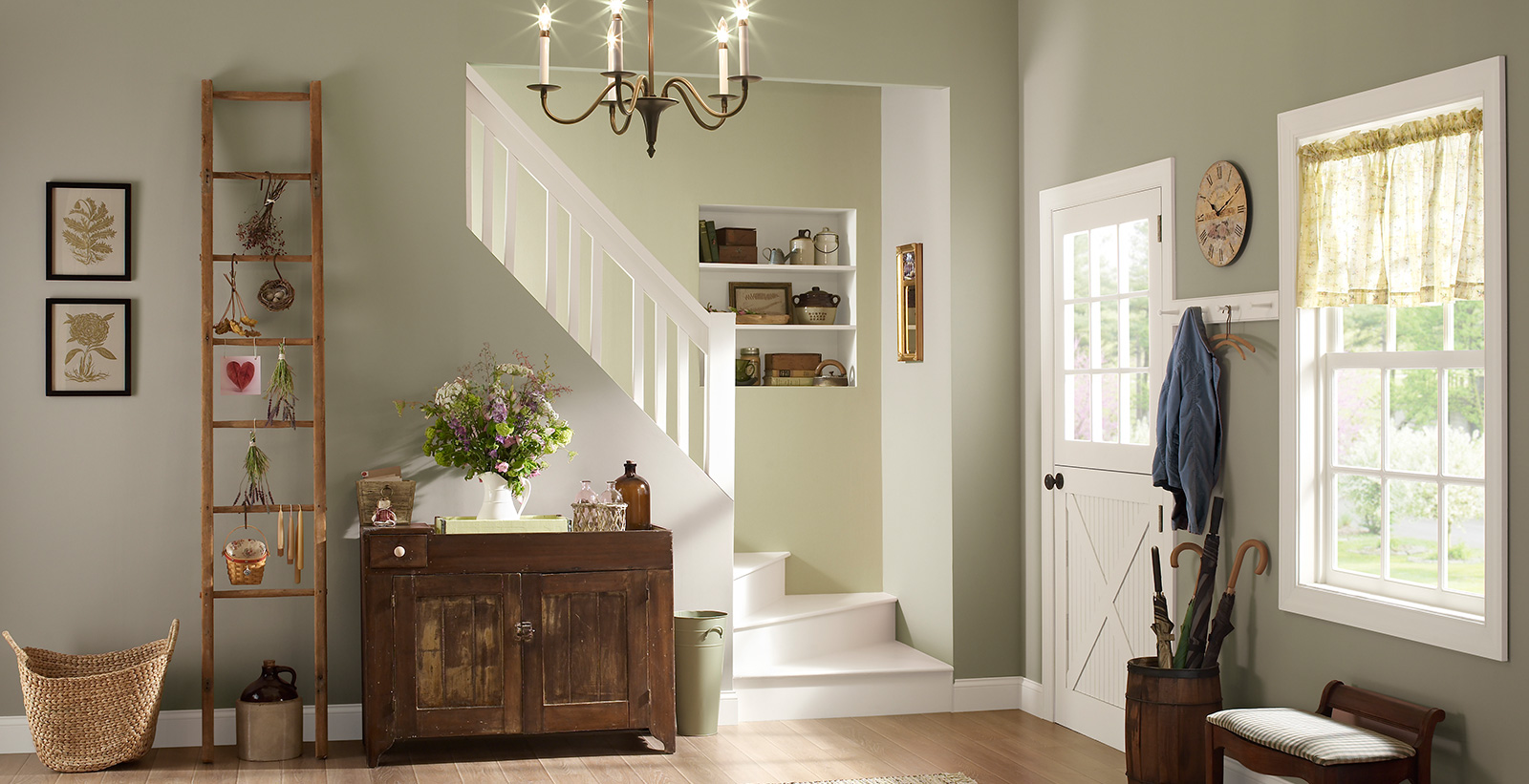 Hallway with stairs, neutral color wall, and white trim, cottage casual style.
