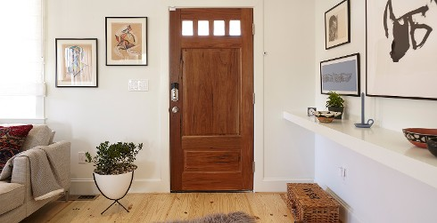 Hallway with white walls, and white trim, wooden door, casual style.