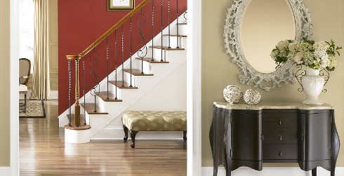 Hallway with stairs, red wall, and white trim, vintage style.
