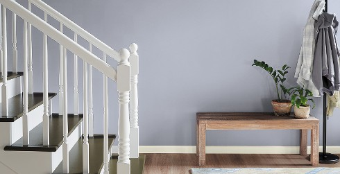 Hallway with stairs, light purple wall, and white trim, relaxed calming style.