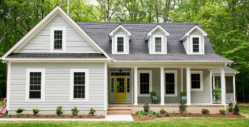 Farmhouse themed cottage house with light gray walls, white trim, and yellow door.