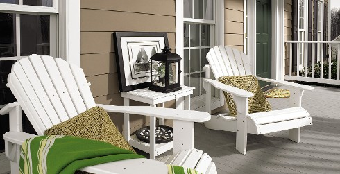 Beach outdoor porch with brown walls, white trim, white beach chairs, and green door.