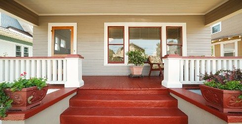Inspirational house porch with red stairs, red flooring, white fencing, neutral walls, red planters and white trim.