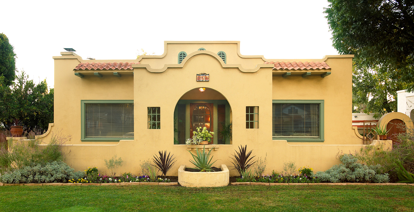 Spanish mediterranean themed house with yellow walls, and green trim.