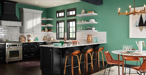 Contemporary kitchen with green on walls, black on cabinets and drawers, and a white tile backsplash.