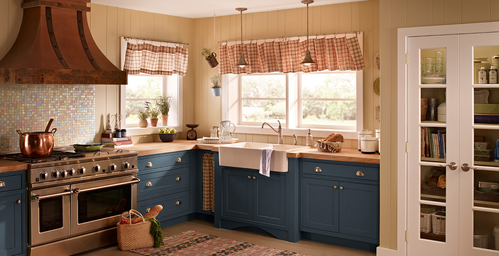 Country styled kitchen with tan on walls, blue on cabinets, and white on pantry and trim.