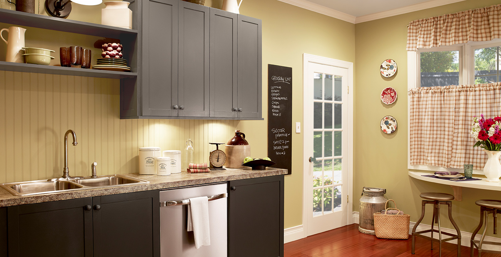 Retro styled kitchen with muted yellow-green on walls, charcoal gray on cabinets, and granite counter tops.