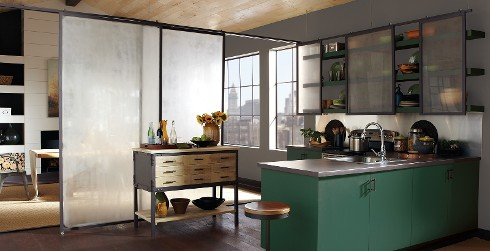 Industrial kitchen with grayish blue accent wall, dark green on cabinets and two-panel room divider