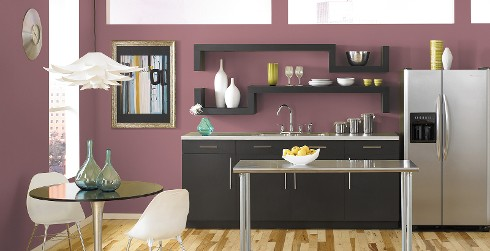 Modern styled kitchen with purple on walls, dark gray on cabinets, and round dining table with bucket chairs