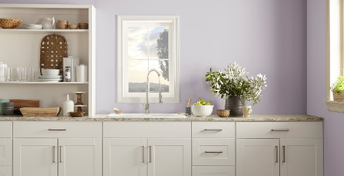 Casually styled kitchen with light lilac on walls, white on cabinets, and white built-in shelving on countertop