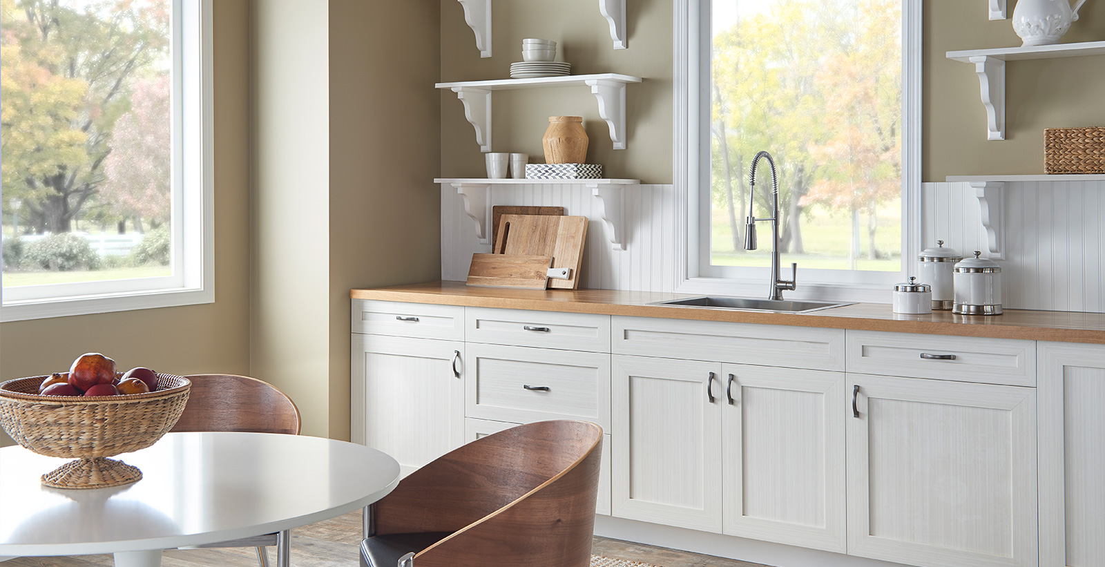 Casual kitchen with tan on wallls, white on cabinets and trim, and wooden counter top