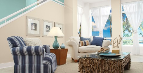 Coastal styled living room with off white on walls, white on trim, and light blue accent wall along staircase