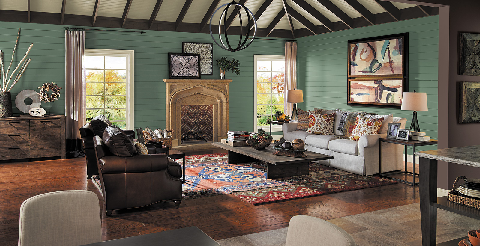 Open concept living room with muted green on walls, off white couch, dark brown leather chairs and dark wood coffee table