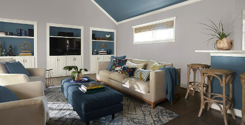 Casual living room with light gray on walls, blue on ceiling, white on trim and cabinets, and light tan upholstered chairs and couch