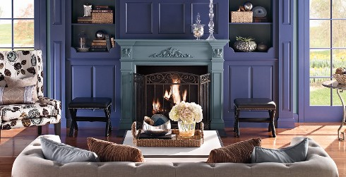 Eclectic styled living room with bright blue on walls, slate blue on fireplace, and light taupe tufted couch