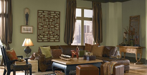 Global styled living room with muted green on walls, dark gray on trim, dark brown leather couch, and wood coffee table