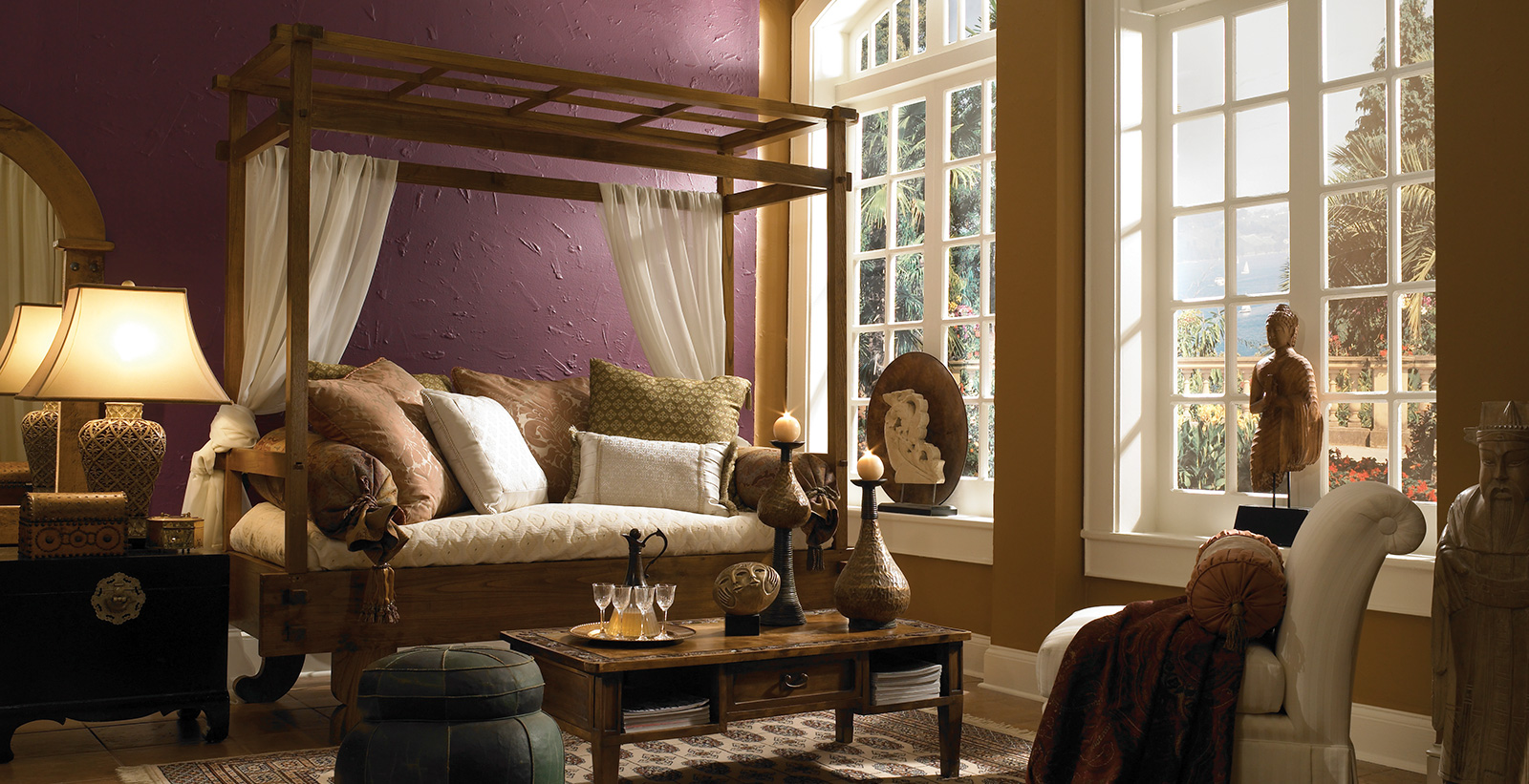 Global inspired living room with purple on main walls, gold on accent wall, white on trim, and 4 poster canopy daybed