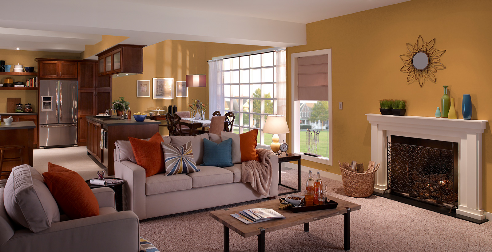Open concept living room with dark mustard on walls, white on trim and fireplace and light taupe couch and chair
