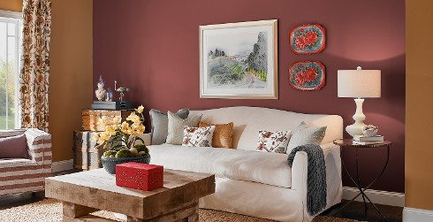 Country styled living room with bronze on main walls, magenta on accent wall, white couch and wood coffee table