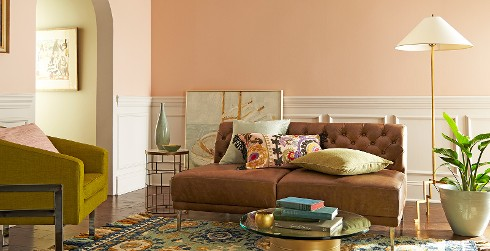 Two tone living room with light peach on top half of walls, off white on bottom half, brown tufted couch, and glass coffee table