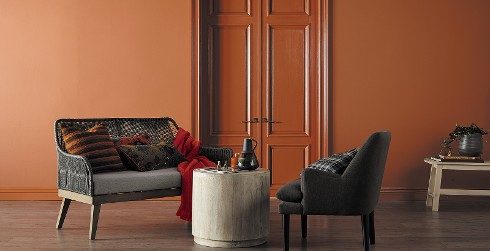 Simple styled living room with burnt orange on walls, dark gray chair and rattan sofa, and wood flooring