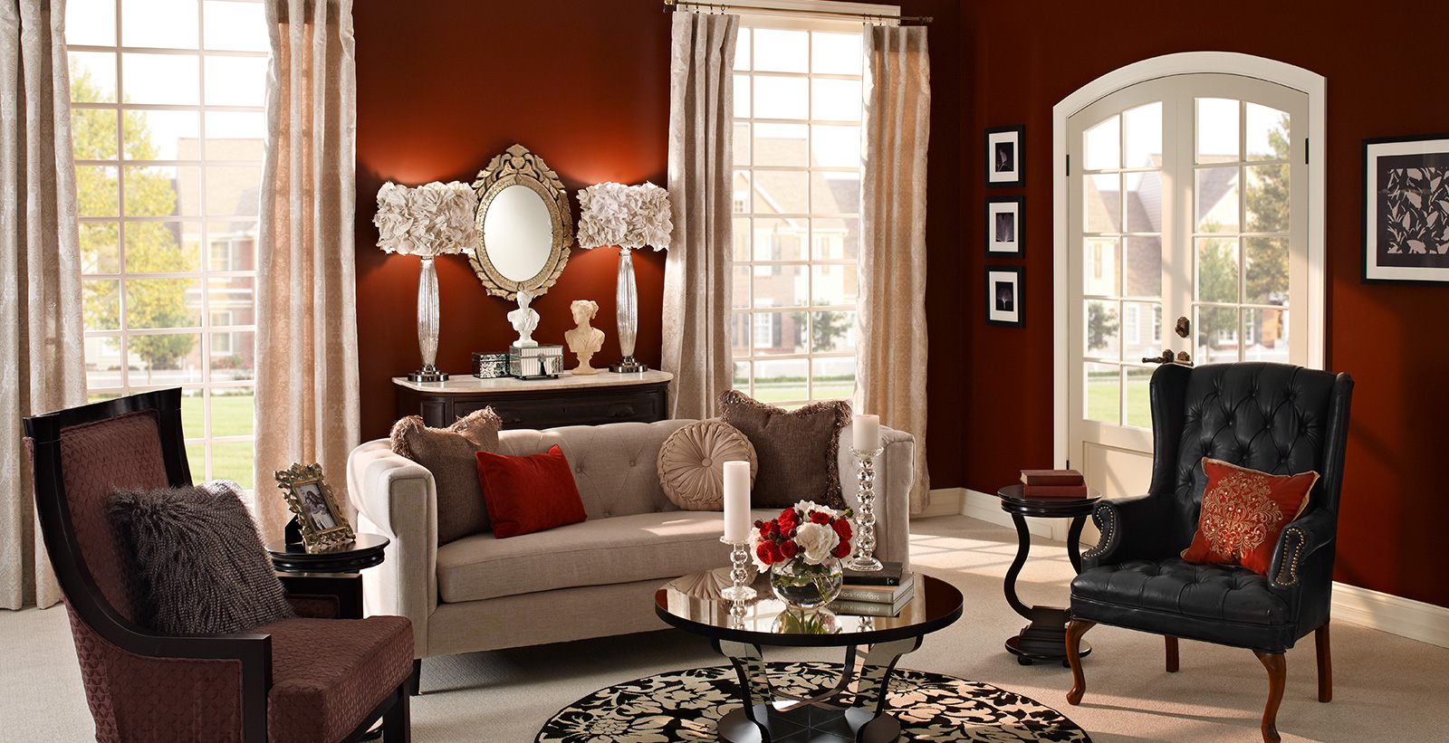 Formal living room with deep red on walls, white on trim, light tan tufted couch, and black round coffee table