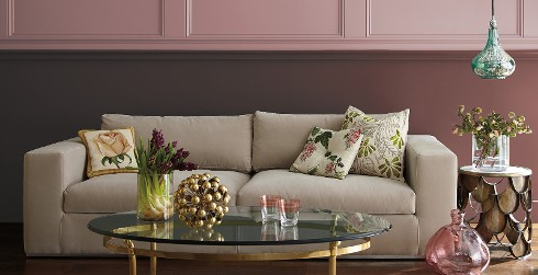 Shabby chic styled living room with mauve pink on top half of walls, magenta on bottom half, light beige couch, and floral throw pillows