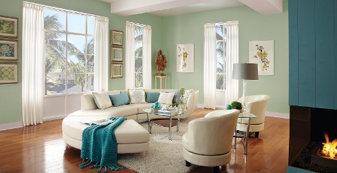 Coastal living room with pale green on main walls, white on trim, teal on wall with fireplace, and cream couch and chairs