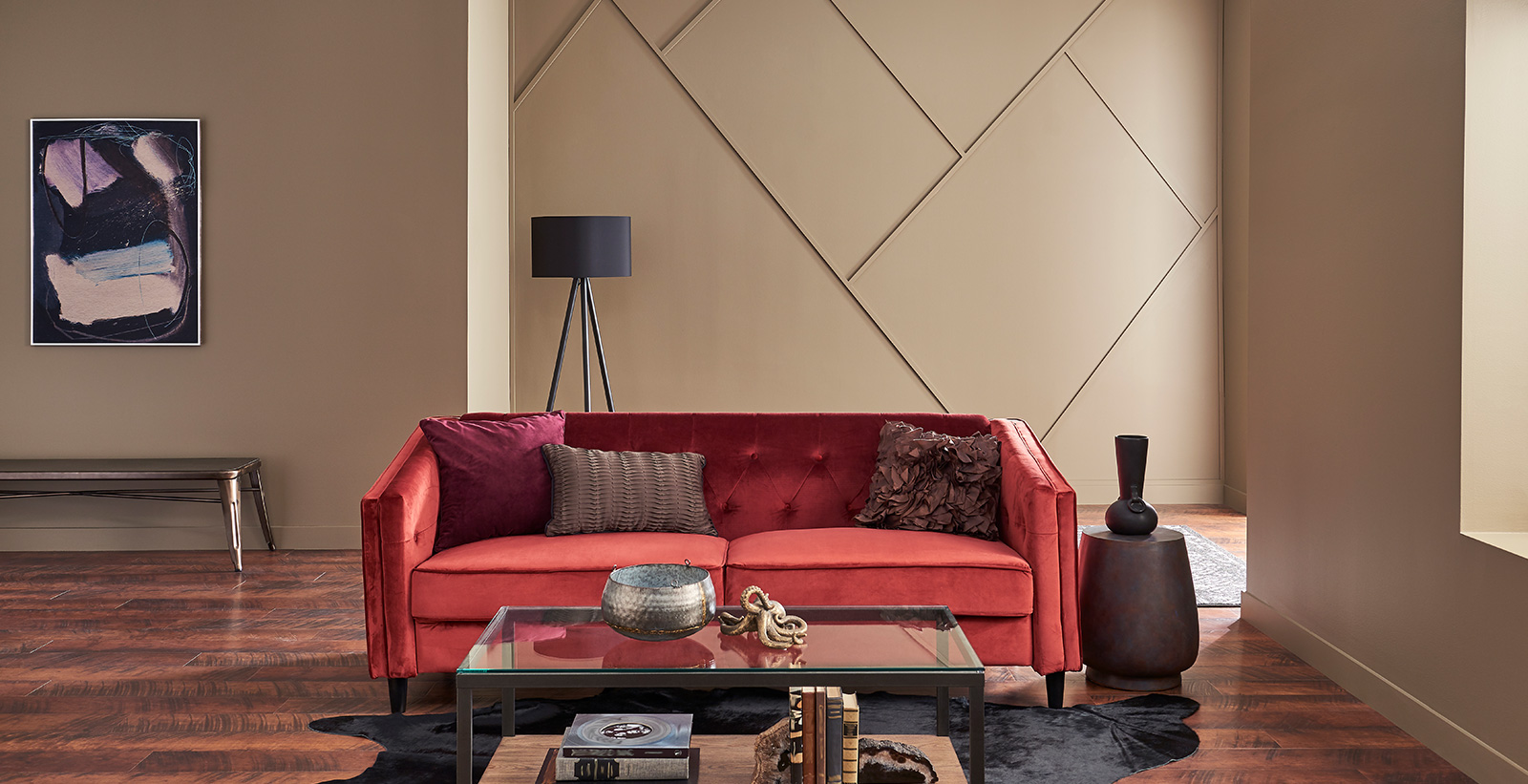 Monochromatic living room with taupe on walls, red tufted couch, glass coffee table, and dark wood flooring