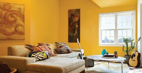 Bright living room with bright yellow on walls, white on trim, tan couch, and metallic round coffee table
