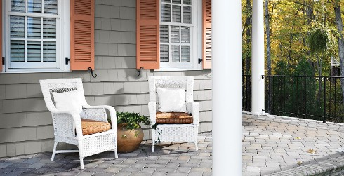 Two white wicker chairs on a stone front proch.