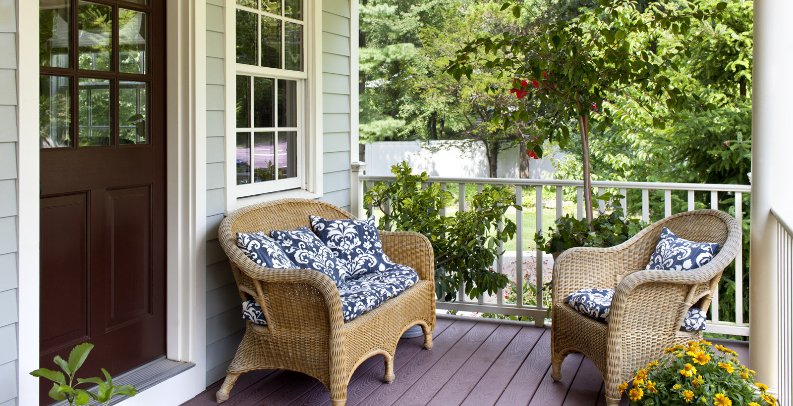 Wicker loveseat and chair on a wooden porch.