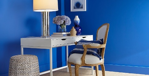 Office workspace with blue walls, and white trim, white desk, bold style.