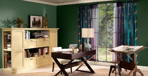 Office workspace with green walls, white trim, and wood furniture, bold and dramatic style.
