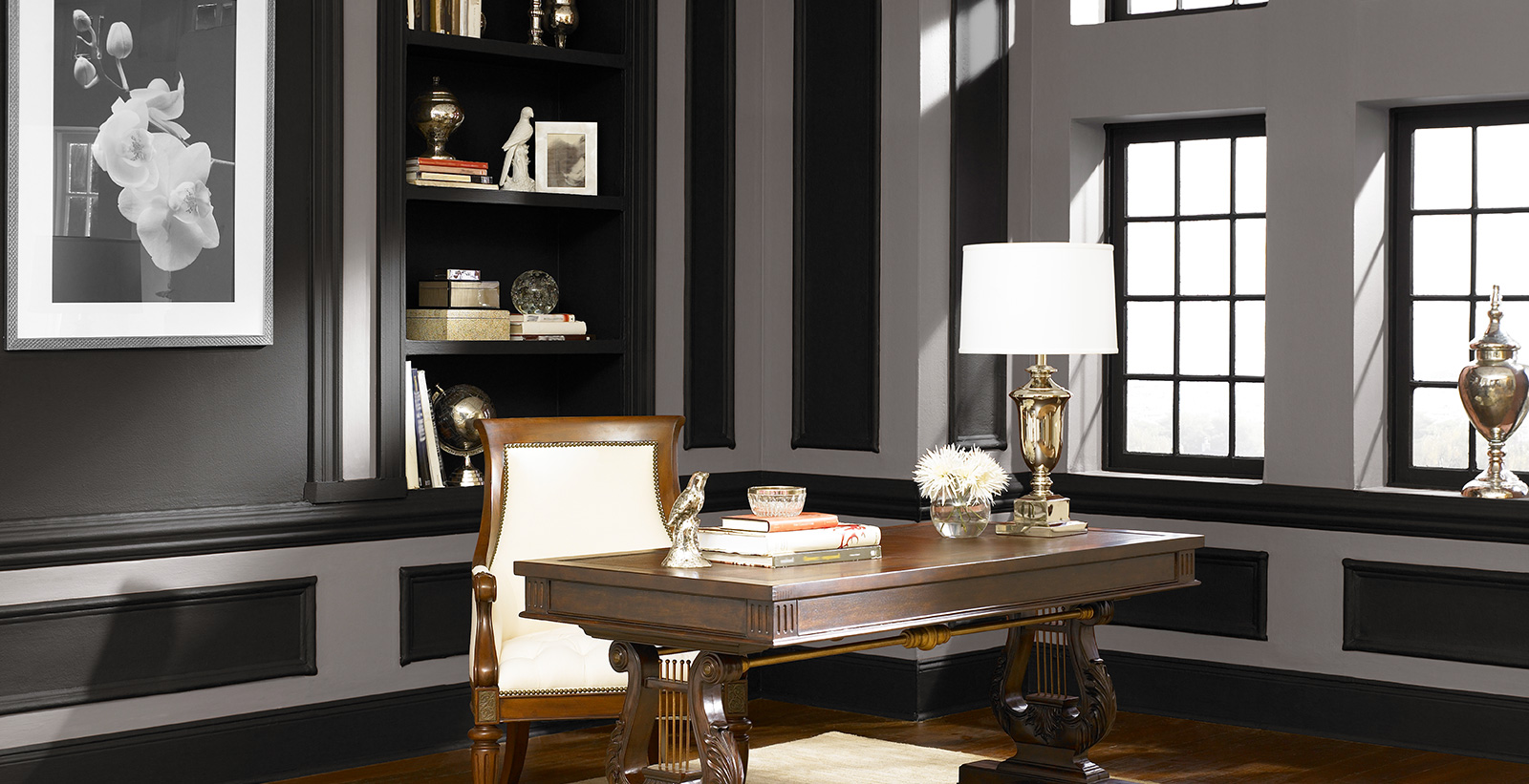 Office workspace with white walls, black trim, and wood furniture, classic style.