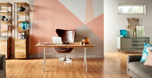 Mid century office workspace with pink patterned wall, and white trim, wooden desk, eclectic style.