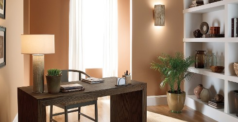 Elemental office workspace with orange walls, and white trim, wooden desk, inviting and friendly style.