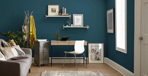 Relaxed office workspace with blue walls, and white trim, wooden desk.