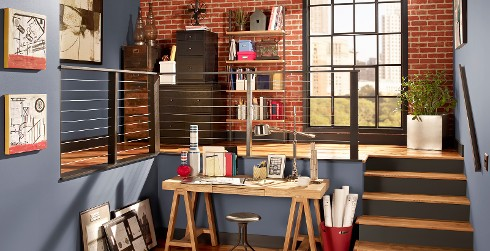 Industrial office workspace with blue walls and brown trim, wooden desk, relaxed and calming style.