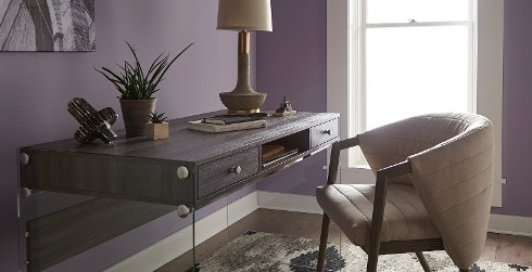 Office workspace with purple walls and white trim, wooden desk, relaxed and calming style.