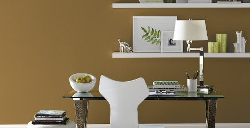 Office workspace with gold wall and white trim, glass desk.