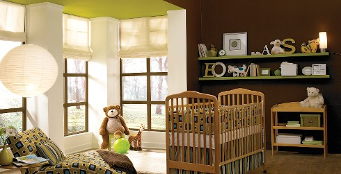 Casual styled youth nursery room with dark brown on walls, white on the trim, green on the ceiling, and brown wooden crib.