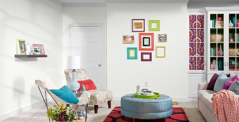 Casual styled youth room with white on walls, white on the trim, white book shelf, and colorful hanging picture frames.